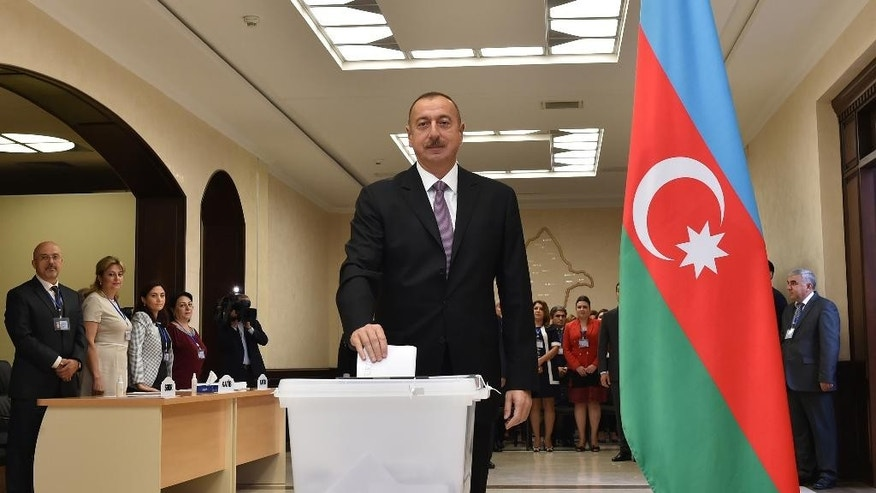 Azerbaijani President Ilham Aliyev casts his ballot at a polling station during a referendum in Baku, Azerbaijan on Monday, Sept. 26, 2016. The Monday vote is on proposals including raising the presidential term from five years to seven, granting the president the right to dissolve parliament and creating new appointed vice presidential posts. (AP Photo/Vugar Amrullayev)