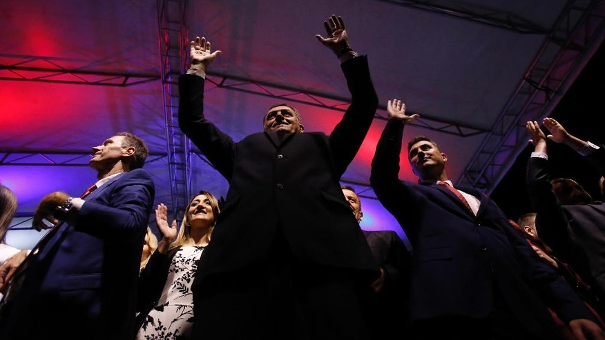 Bosnian Serb Milorad Dodik, President of the Bosnian Serb region of Republic of Srpska, greets supporters during celebrations after the result of the referendum in the Bosnian town of Pale, Bosnia, on Sunday Sept. 25, 2016. Sunday's vote asks residents of Republika Srpska whether to maintain a national holiday on Jan. 9, despite a ruling of Bosnia's constitutional court that the date discriminates against non-Serbs. (AP Photo/Amel Emric)