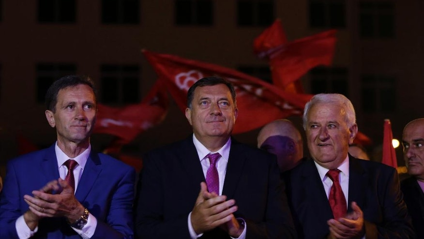 Bosnian Serb Milorad Dodik, centre, President of the Bosnian Serb region of Republic of Srpska, Bosko Tomic, left, and Bosko Jugovic, right, greet supporters during celebrations after the result of the referendum in the Bosnian town of Pale, Bosnia, on Sunday Sept. 25, 2016. Sunday's vote asks residents of Republika Srpska whether to maintain a national holiday on Jan. 9, despite a ruling of Bosnia's constitutional court that the date discriminates against non-Serbs. (AP Photo/Amel Emric)