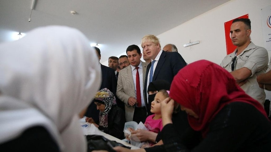 British Foreign Secretary Boris Johnson, center, is surrounded by Turkish officials during his visit to the Syrian refugee camp in Nizip in Gaziantep province, Turkey, Monday, Sept. 26, 2016. Johnson is on a three-day visit to Turkey. (Ensar Ozdemir/Anadolu Agency Pool via AP )