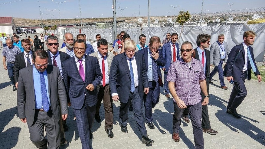 British Foreign Secretary Boris Johnson, center, is surrounded by Turkish officials during his visit to the Syrian refugee camp in Nizip in Gaziantep province, Turkey, Monday, Sept. 26, 2016. Johnson is on a three-day visit to Turkey.(Ali Ihsan Ozturk/Anadolu Agency Pool via AP )