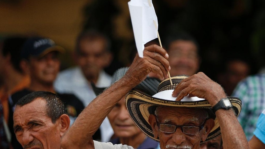 An elderly man places a white flag on his hat during a concert for peace in Carmen de Bolivar, Colombia, Sunday, Sept. 25, 2016. Colombia's government and the Revolutionary Armed Forces of Colombia, FARC, will sign a peace agreement to end over 50 years of conflict, in Cartagena, on Monday. (AP Photo/Fernando Vergara)