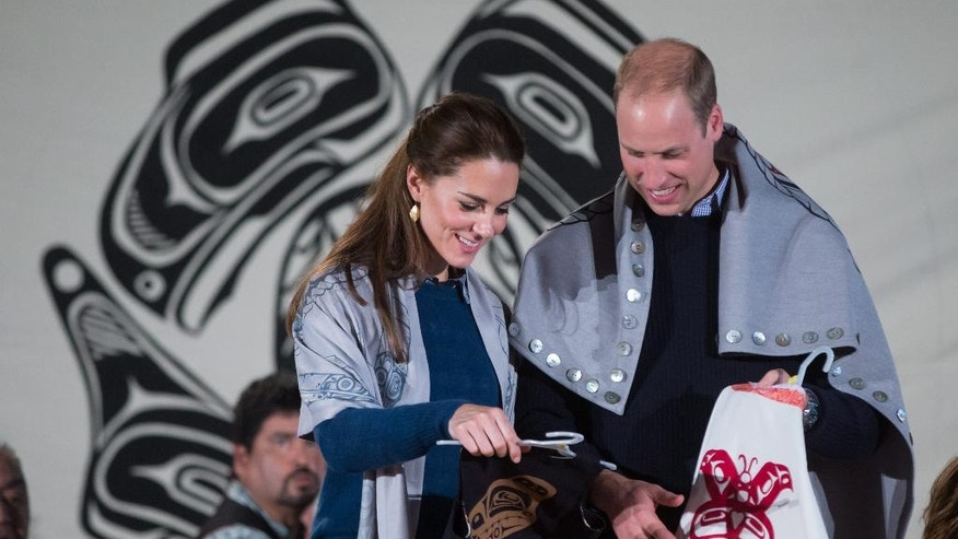 Draped in traditional First Nation blankets, Britain's Prince William, the Duke of Cambridge, and Kate, the Duchess of Cambridge, hold vests they were presented with for Prince George and Princess Charlotte during a welcoming ceremony at the Heiltsuk First Nation in the remote community of Bella Bella, Canada, Monday, Sept. 26, 2016. (Darryl Dyck/The Canadian Press via AP)