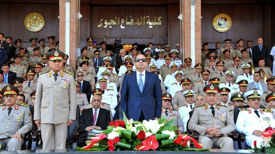 FILE - In this picture provided by the office of the Egyptian Presidency, Egyptian President Abdel-Fattah el-Sissi, center, and Defense Minister Sedqi Sobh, left, stand to attention while other members of the military look on at the Air Defense Academy in Alexandria, Egypt. Egypt's president has indignantly rejected criticism that the country's military is being distracted from its core duties by further involving itself in the economy.  (Mohammed Samaha/Egyptian Presidency via AP, File)
