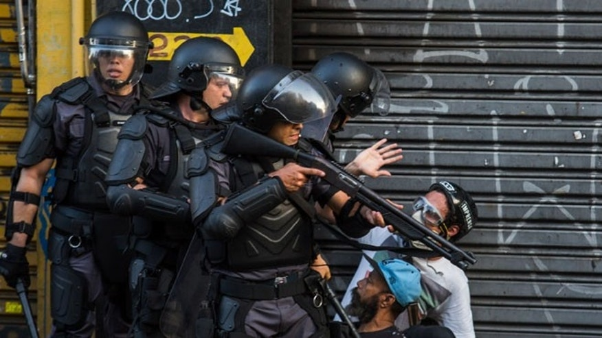 SAO PAULO, BRAZIL - JANUARY 9: Police arrest protesters during a protest organized by Members of Movimento Passe Livre (Free Pass Movement) against the increase in bus and subway fares, which now costs 3.50 Reais ($1.30 USD) on January 9, 2015  in Sao Paulo, Brazil. The group was responsible for the wave of massive protests that erupted in the country in June 2013. (Photo by Victor Moriyama/Getty Images)