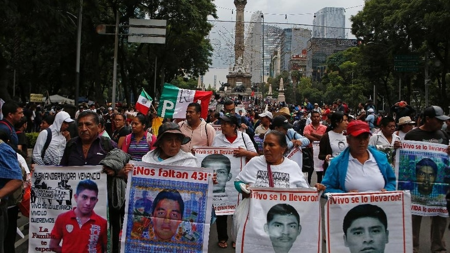 Parents of the 43 missing students march holding images of their sons during a protest march in Mexico City, Monday, Sept. 26, 2016. The march was held  on the second anniversary of the disappearance, on Sept. 26, 2014, of the students from the Rural Normal School at Ayotzinapa. The government's initial investigation decided the students were killed and incinerated in a fire. But international experts have cast doubt on this theory and the families have not accepted it. (AP Photo/Eduardo Verdugo)