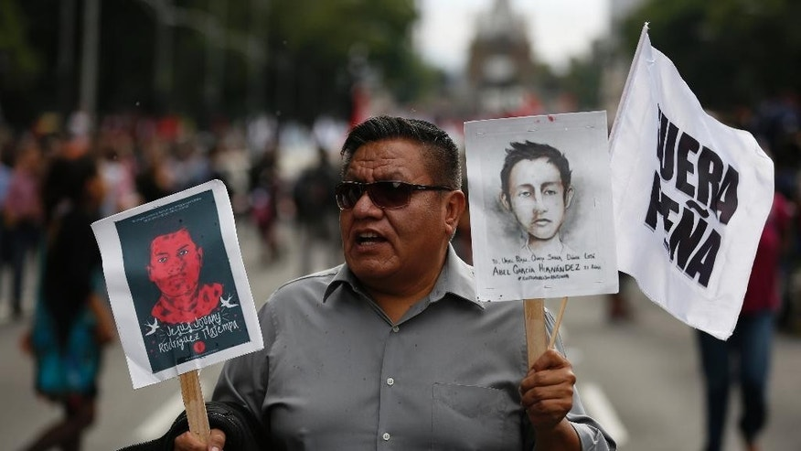 "A man carries portraits of two of the 43 missing students along with a sign that reads in Spanish ""Pena Out,"" referring to Mexican President Enrique Pena Nieto, during a protest march in Mexico City, Monday, Sept. 26, 2016. The march was held  on the second anniversary of the disappearance, on Sept. 26, 2014, of the students from the Rural Normal School at Ayotzinapa. The government's initial investigation decided the students were killed and incinerated in a fire. But international experts have cast doubt on this theory and the families have not accepted it. (AP Photo/Eduardo Verdugo)"