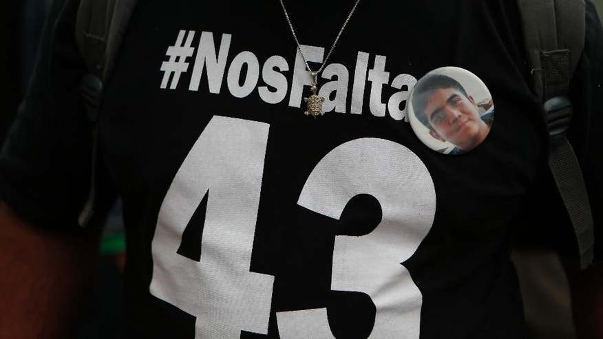 "A man wears a T-shirt with a hashtag saying ""We are missing 43"" and a pin with the image of one of the 43 missing students during a protest march in Mexico City, Monday, Sept. 26, 2016. The march was held  on the second anniversary of the disappearance, on Sept. 26, 2014, of the students from the Rural Normal School at Ayotzinapa. (AP Photo/Eduardo Verdugo)"
