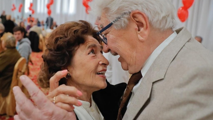 Silvia and Liciniu Agapi, a couple married for 52 and a half years, dance at a party organized by a district city hall in Bucharest, Romania, Monday, Sept. 26, 2016. A district of the Romanian capital celebrated hundreds of couples, more than 600 people, who have been married for at least half a century by handing out cash awards of 1,000 lei ($255) and inviting them to a joint lunch. (AP Photo/Vadim Ghirda)
