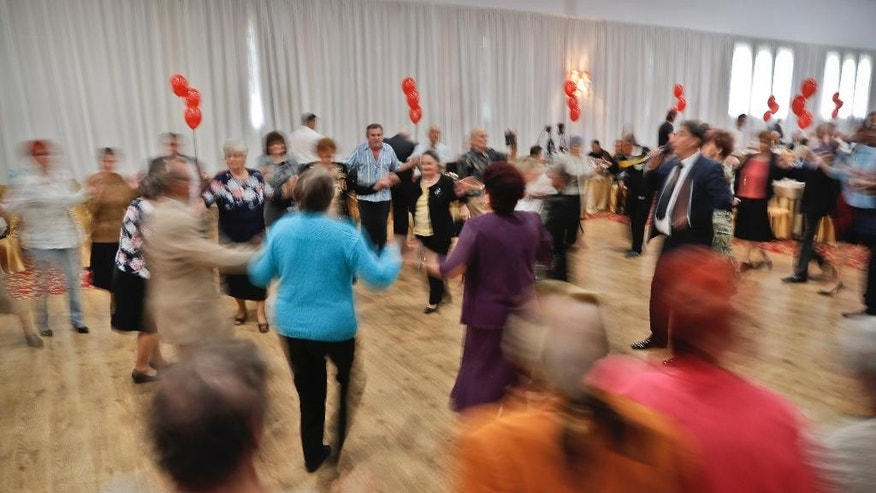 Romanian couples who have been married for at least 50 years dance at a party organized by a district city hall in Bucharest, Romania, Monday, Sept. 26, 2016. A district of the Romanian capital celebrated hundreds of couples, more than 600 people, who have been married for at least half a century by handing out cash awards of 1,000 lei ($255) and inviting them to a joint lunch. (AP Photo/Vadim Ghirda)
