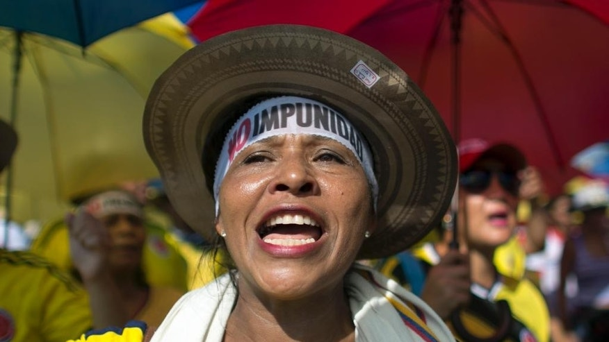 "A demonstrator yells ""No to the plebiscite"" to protest the government's peace agreement with the Revolutionary Armed Forces of Colombia (FARC), to be signed later in the day in Cartagena, Colombia, Monday, Sept. 26, 2016. Colombians will be given the final say on endorsing or rejecting the accord in an Oct. 2 referendum. (AP Photo/Ariana Cubillos)"