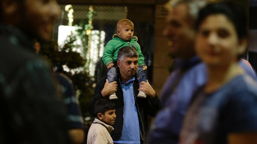 Syrian refugee Fadi Ehmood, center, waits with his children at Omonia square in Athens before heading to the airport for a flight to Madrid on Monday, Sept. 26, 2016. A group of 27 Syrians and four Iraqis was among the very few accepted by a European country as part of a sputtering relocation program designed to relieve pressure on Greece and Italy, the main entry points for those fleeing war and hoping for better lives in the European Union. (AP Photo/Thanassis Stavrakis)