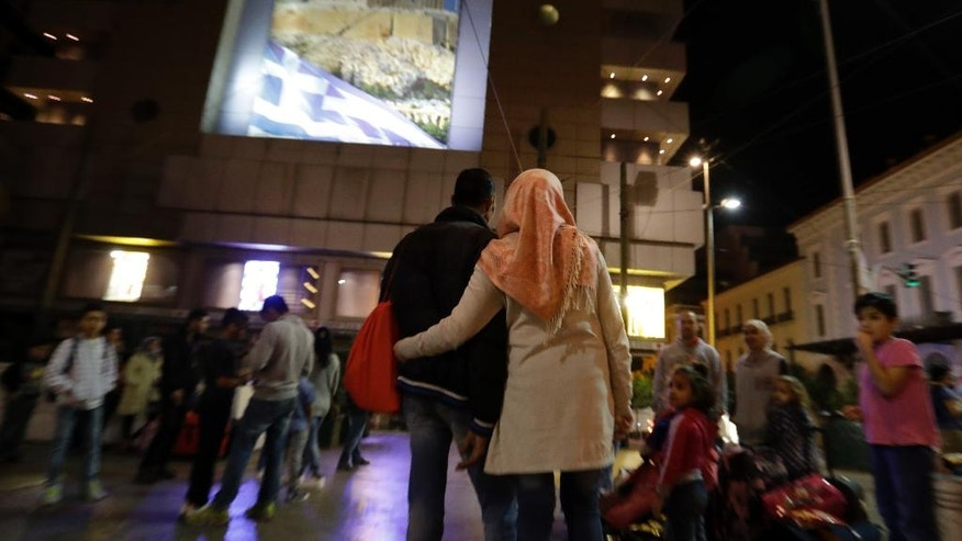 Refugees wait under an advertising banner, depicting Acropolis and the Greek flag, at Omonia square in Athens before heading to the airport for a flight to Madrid on Monday, Sept. 26, 2016. A group of 27 Syrians and four Iraqis was among the very few accepted by a European country as part of a sputtering relocation program designed to relieve pressure on Greece and Italy, the main entry points for those fleeing war and hoping for better lives in the European Union. (AP Photo/Thanassis Stavrakis)