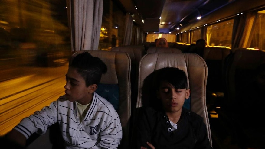 A boy looks the coach route while another one sleeps as they head to the Athens airport for a flight to Madrid on Monday, Sept. 26, 2016. A group of 27 Syrians and four Iraqis was among the very few accepted by a European country as part of a sputtering relocation program designed to relieve pressure on Greece and Italy, the main entry points for those fleeing war and hoping for better lives in the European Union. (AP Photo/Thanassis Stavrakis)