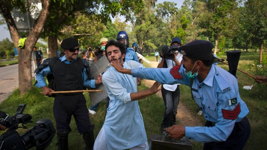 "FILE - In this Friday, Sept, 21, 2012 file photo, Pakistani police officers beat a protestor during clashes in Islamabad, Pakistan. Human Rights Watch says Pakistan's corrupt and ill-equipped police system encourages serious rights violations, including arbitrary arrests, torture and ""encounter killings"" in which police stage shootouts to kill individuals in custody. (AP Photo/Anjum Naveed, File)"