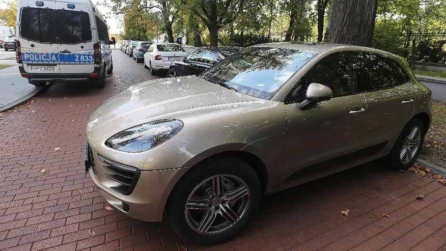 A Porsche car on Moscow registration plates parked near the office of Prime Minister Beata Szydlo in Warsaw, Poland, Monday, Sept. 26, 2016, shortly after its driver, a Russian citizen, was detained by the police for illegally flying a drone over the government and president's buildings. The car was later escorted away by the police. (AP Photo/Czarek Sokolowski)