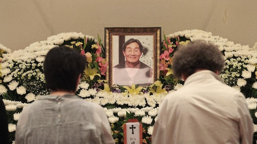 Mourners pay tributes in front of a memorial altar for the late farmer activist Baek Nam-gi at the Seoul National University Hospital in Seoul, South Korea, Monday, Sept. 26, 2016. Dozens of activists are commemorating Baek who died in the hospital almost a year after being knocked unconscious by water cannons during protests against South Korea's government. (AP Photo/Ahn Young-joon)