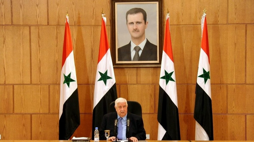 FILE -- In this In this March 12, 2016 file photo released by the Syrian official news agency SANA, Syrian Foreign Minister Walid al-Moallem sits beneath a portrait of Syrian President Bashar Assad as he speaks during a press conference in Damascus, Syria. An internationally-brokered cease-fire for Syria is still viable, Syrian Foreign Minister Walid al-Moallem said in a TV interview broadcast Monday, Sept. 26, 2016, and President Bashar Assad's administration is prepared to take part in a unity government. The interview on Mayadeen TV came as rescue workers in Aleppo cleaned up from what they said were the worst airstrikes on rebel-held areas of the northern city in five years. (SANA via AP, File)