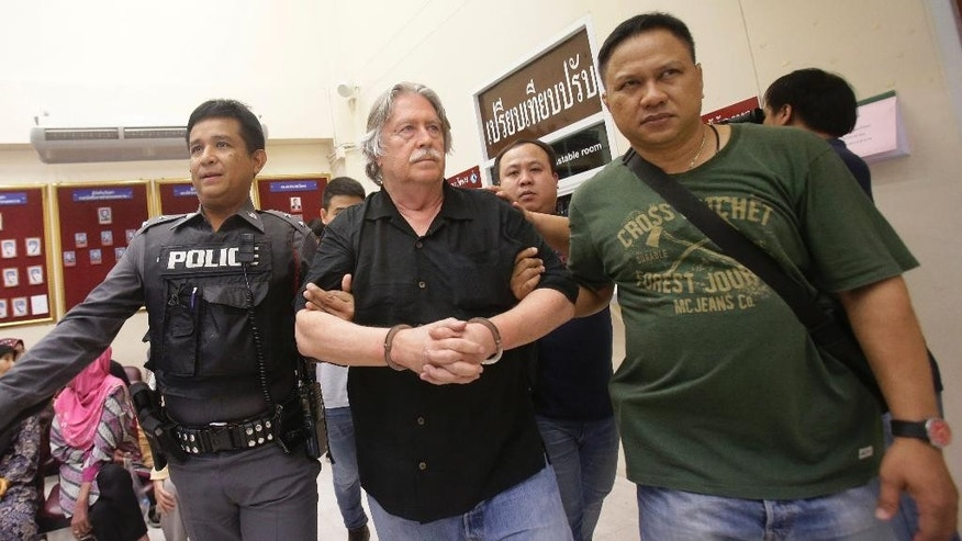 In this Saturday, Sept. 24, 2016 photo, Thai policemen escort a suspect, center, after three men were arrested on charges of trafficking in forged passports and  concealing a dismembered body at an apartment in Bangkok, Thailand. Thai police are seeking to identify the corpse found in a freezer when they raided the apartment and arrested two Americans and a Briton. (AP Photo/Sakchai Lalit)