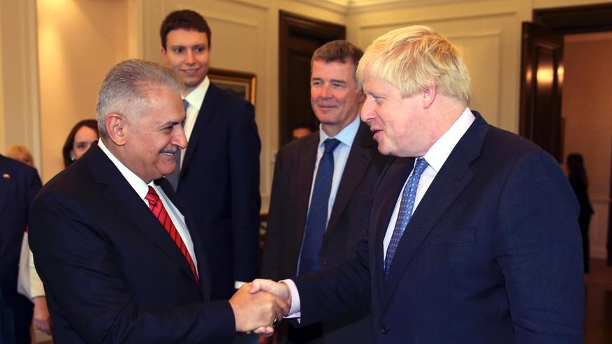 Turkey's Prime Minister Binali Yildirim, left, greets British Foreign Secretary Boris Johnson before a meeting in Ankara, Turkey, Tuesday, Sept. 27, 2016. Johnson said Monday Britain would continue to support Turkey's bid to join the European Union even after Britain leaves the bloc. Johnson also said Turkey and Britain were united in the fight against terrorism.(Hakan Goktepe, Prime Ministry Press Service, Pool via AP Photo)