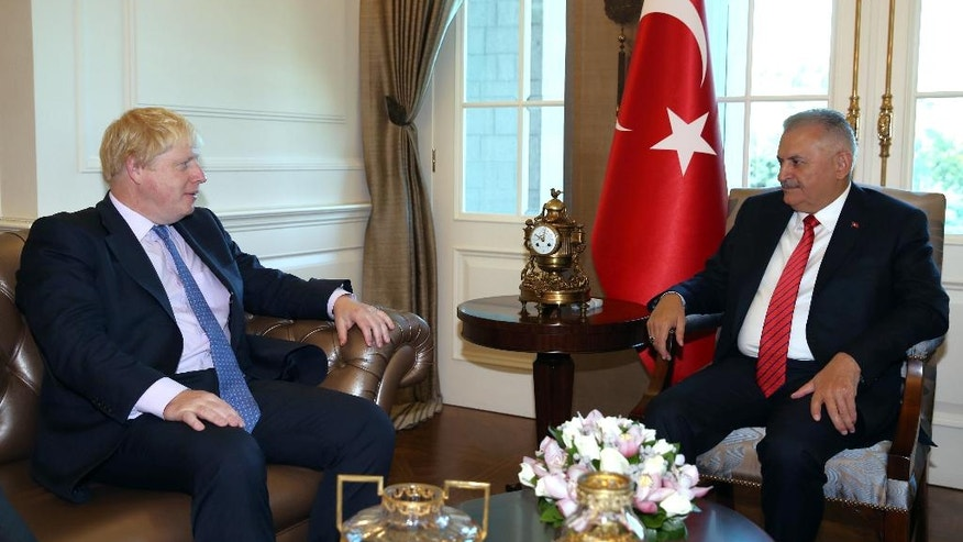 Turkey's Prime Minister Binali Yildirim, right, and British Foreign Secretary Boris Johnson speak during a meeting in Ankara, Turkey, Tuesday, Sept. 27, 2016. Johnson said Monday Britain would continue to support Turkey's bid to join the European Union even after Britain leaves the bloc. Johnson also said Turkey and Britain were united in the fight against terrorism. (Hakan Goktepe/Prime Ministry Press Service, Pool via AP Photo)