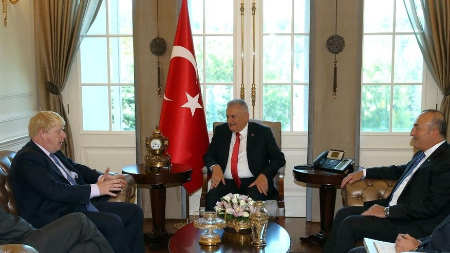 Turkey's Prime Minister Binali Yildirim, center, Turkish Foreign Minister Mevlut Cavusoglu, right, and British Foreign Secretary Boris Johnson speak during a meeting in Ankara, Turkey, Tuesday, Sept. 27, 2016. Johnson said Monday Britain would continue to support Turkey's bid to join the European Union even after Britain leaves the bloc. Johnson also said Turkey and Britain were united in the fight against terrorism.(Hakan Goktepe/Prime Ministry Press Service, Pool via AP Photo)