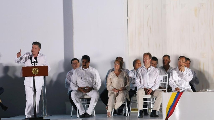 Colombia's President Juan Manuel Santos, left, delivers a speech after he signed a peace agreement between Colombia's government and the Revolutionary Armed Forces of Colombia, FARC, in Cartagena, Colombia, Monday, Sept. 26, 2016. Colombians are being given the final say on endorsing or rejecting the accord in an Oct. 2 referendum. (AP Photo/Fernando Vergara)