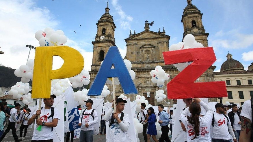 "People hold up letters that form the word ""Peace"" in Spanish during a gathering at Bolivar square in Bogota, Colombia, Monday, Sept. 26, 2016. Colombia's government and the Revolutionary Armed Forces of Colombia signed a peace agreement to end over 50 years of conflict, in Cartagena. (AP Photo/ Jennifer Alarcon)"