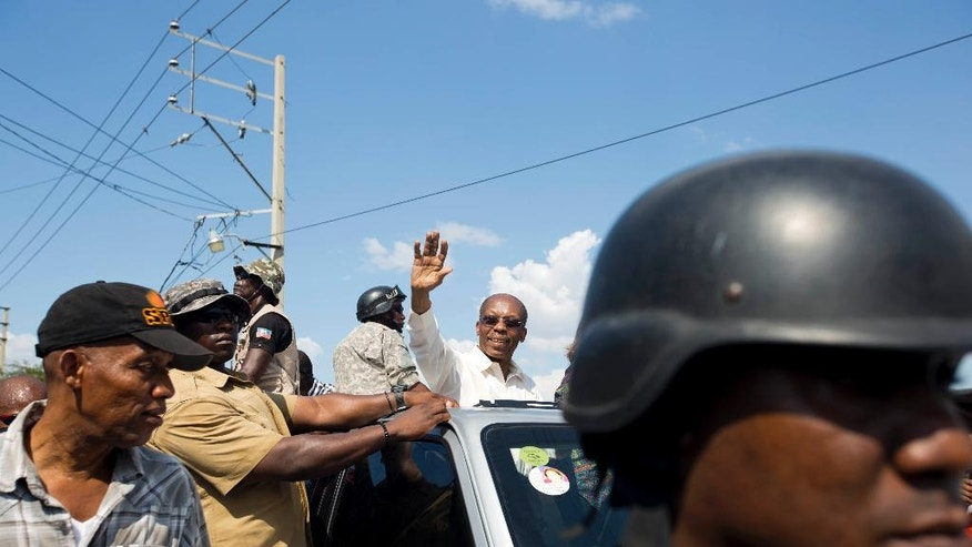 In this Sept. 21, 2016 photo, Haiti's former President Jean-Bertrand Aristide greets supporters as he campaigns with presidential candidate Maryse Narcisse, of the Fanmi Lavalas political party, in Port-au-Prince, Haiti. Aristide has leaped from behind the scenes to take a major role in campaigning for next month's presidential election, leading many to believe that the most polarizing figure in the tumultuous world of Haitian politics is poised to regain influence if his party wins the Oct. 9 elections. (AP Photo/Dieu Nalio Chery)