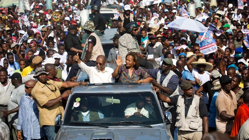 "In this Sept. 21, 2016 photo, Haiti's former President Jean-Bertrand Aristide, left, waves to supporters as he campaigns with presidential candidate Maryse Narcisse, of the Fanmi Lavalas political party, in Port-au-Prince, Haiti. ""He's the king of kings! Seeing him on the streets is like being in paradise,"" Port-au-Prince resident Jhony Narcisse said as he jogged to keep up with Aristide's motorcade during the rally. Haiti will hold elections on Oct. 9. (AP Photo/Dieu Nalio Chery)"