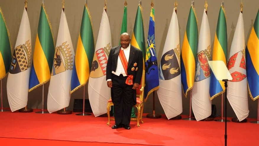 Gabon's President Ali Bongo Ondimba stands on stage as he is sworn in for a second term in Libreville. Gabon, Tuesday, Sept. 27, 2016 Gabon's President Ali Bongo Ondimba has been sworn in for a second seven-year term, extending a family dynasty in place for decades after a disputed vote saw his re-election by a slim margin.(AP Photo/Jeremi Mba)