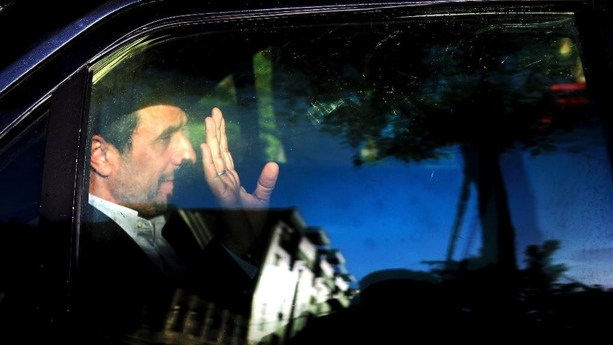 "FILE-- In this file photo taken on Monday, Aug. 3, 2015, former Iranian President Mahmoud Ahmadinejad waves from his car outside his house in northeastern Tehran, Iran. An adviser to Mahmoud Ahmadinejad, Iran's former hard-line president, says the politician won't seek re-election in next year's presidential vote after apparently being discouraged by the country's supreme leader. In comments reported Monday, Khamenei was quoted as saying he recommended an unnamed candidate not seek office as it would spark a ""polarized situation"" that would be ""harmful for the county."" (AP Photo/Ebrahim Noroozi, File)"
