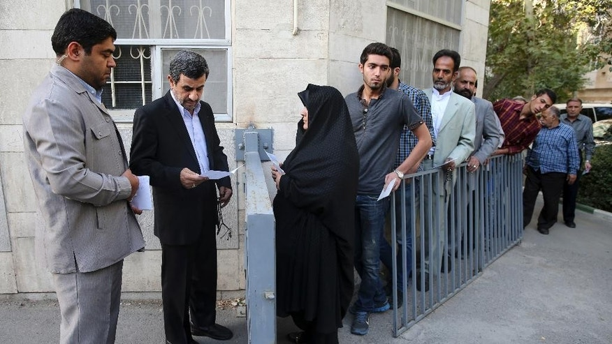"FILE---In this file photo taken on Monday, Aug. 3, 2015, former Iranian President Mahmoud Ahmadinejad, second left, reads a petition for help from a woman while others wait in queue outside his house in northeastern Tehran, Iran. An adviser to Mahmoud Ahmadinejad, Iran's former hard-line president, says the politician won't seek re-election in next year's presidential vote after apparently being discouraged by the country's supreme leader. In comments reported Monday, Khamenei was quoted as saying he recommended an unnamed candidate not seek office as it would spark a ""polarized situation"" that would be ""harmful for the county."" (AP Photo/Ebrahim Noroozi, File)"