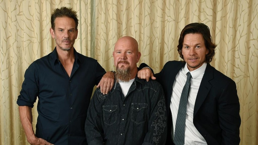 """In this Sept. 13, 2016 photo, Mike Williams, center, an electrician and survivor on the Deepwater Horizon oil rig, poses with Peter Berg, left, director of the film """"Deepwater Horizon,"""" and cast member Mark Wahlberg at the Ritz-Carlton Hotel in Toronto. Berg's film is not about the environmental disaster of the Gulf of Mexico oil leak, nor an exploration of BP's responsibility for the accident. Instead, it's squarely focused on oil rig workers and the 11 who died in the explosion. (Photo by Chris Pizzello/Invision/AP)"""