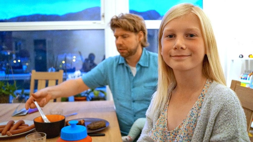 In this photo taken on Sunday, Sept. 11, 2016, 10 year-old Anna Thulin sits down for dinner next to her stepfather Ola Vassbo in Haugesund, Norway. Anna was born a boy but never felt like one. Soon, she is likely to receive a letter confirming that she is legally a girl. Norway recently became the fifth country in the world to allow adults to legally change genders without a doctor's agreement or intervention. Argentina, Ireland and Denmark have similar laws. But only Malta and Norway have extended the liberalized rules to children. (AP Photo/David Keyton)