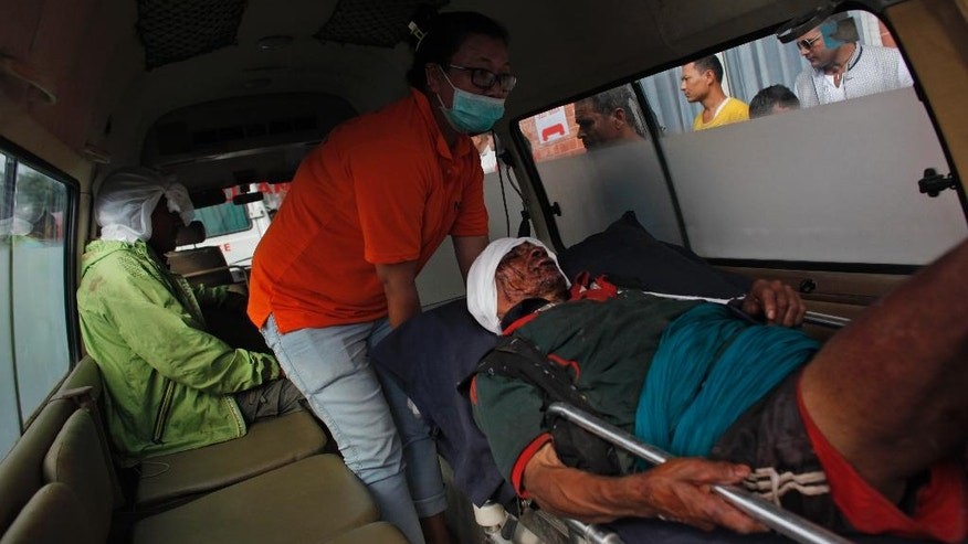 An injured person, rescued after an overcrowded bus slipped off a mountain road is brought for treatment to the Teaching hospital in Kathmandu, Nepal, Tuesday, Sept. 27, 2016. The bus slipped off the road near Lapang Phedi village, 120 kilometers (75 miles) west of Kathmandu, the capital, and rolled about 300 meters (980 feet) before stopping on the banks of the Ankhu River.(AP Photo/Niranjan Shrestha)