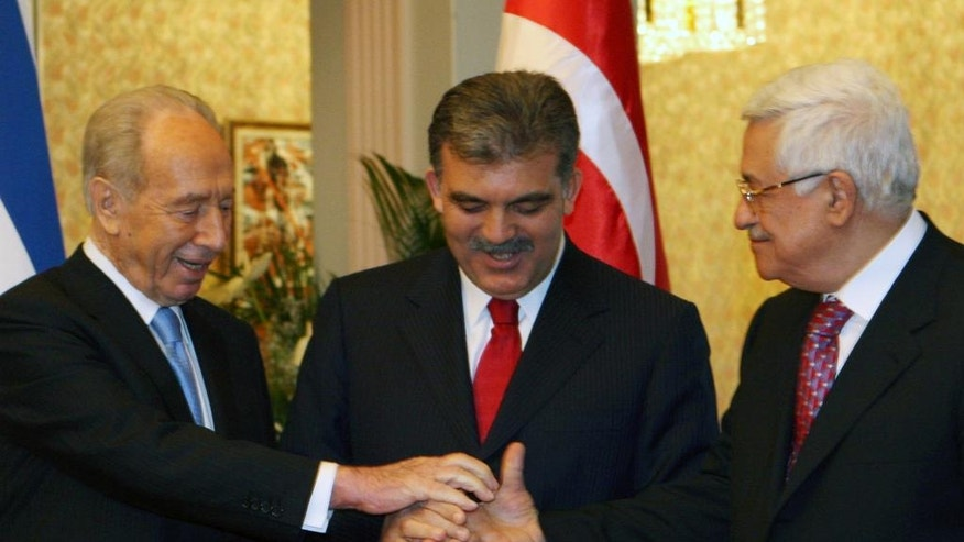 FILE - In this Tuesday, Nov. 13, 2007, file photo, Presidents Shimon Peres of Israel, left, Abdullah Gul of Turkey, center, and President of the Palestinian Authority Mahmoud Abbas try to reach hands as they pose for cameras after their meeting in Ankara. Peres, a former Israeli president and prime minister, whose life story mirrored that of the Jewish state and who was celebrated around the world as a Nobel prize-winning visionary who pushed his country toward peace, has died, the Israeli news website YNet reported early Wednesday, Sept. 28, 2016. He was 93. (AP Photo/Burhan Ozbilici, File)