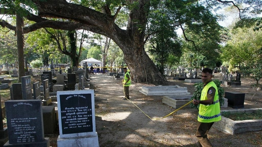 Sri Lankan crime investigating police officers prepare to exhume the remains of murdered newspaper editor Lasantha Wickrematunge at a cemetery in Colombo, Sri Lanka, Tuesday, Sept. 27, 2016, following a court order for a fresh investigation. Wickrematunge, editor of the Sunday Leader newspaper, was killed while driving to work in January 2009. He was an investigative journalist who wrote about government corruption and a sharp critic of the then government's alleged human rights violations during a civil war with the ethnic Tamil rebels. (AP Photo/Eranga Jayawardena)