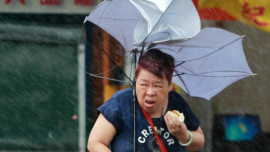 A woman eats and struggles with her umbrella against powerful gusts of wind generated by typhoon Megi across the the island in Taipei, Taiwan, Tuesday, Sept. 27, 2016. Schools and offices have been closed on Taiwan and people in dangerous areas have been evacuated as a large typhoon with 162 kilometers- (100 miles-) per-hour winds approaches the island. (AP Photo/Chiang Ying-ying)