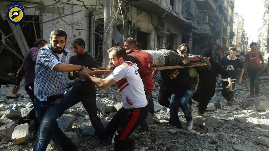 In this photo provided by the Syrian Civil Defense group known as the White Helmets, Syrians carry a victim after airstrikes by government helicopters on the rebel-held Aleppo neighborhood of Mashhad, Syria, Tuesday Sept. 27, 2016. With diplomacy in tatters and a month left to go before U.S. elections, the Syrian government and its Russian allies are using the time to try and recapture the northern city of Aleppo, mobilizing pro-government militias in the Old City and pressing ahead with the most destructive aerial campaign of the past five years. (Syrian Civil Defense White Helmets via AP)