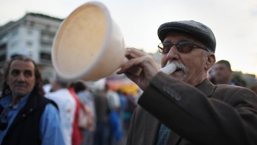 An elderly man participates in a protest outside the Greek Parliament in Athens, Tuesday, Sept. 27, 2016. Greek labor unions are organizing strikes and protests against a plan to place major state assets under the control of a new privatization fund that will be headed by bailout creditors. The fund called the Hellenic Company of Assets and Participations will take control of public utilities and other assets for 99 years if parliament approves draft legislation late Tuesday. (AP Photo/Petros Giannakouris)