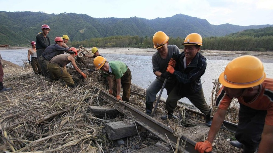 FILE- In this Friday, Sept, 16, 2016, file photo, workers repair the flood-damaged train track between Sinjon and Kanphyong train stations in North Hamgyong Province, North Korea. North Korean soldiers and relief teams rushed to clear roads and railway tracks, build shelters and provide food and sanitation Friday to tens of thousands of residents in a remote part of the country near the Chinese border that was devastated by heavy downpours and flash-floods when a typhoon pounded their villages last week. (AP Photo/Kim Kwang Hyon, File)