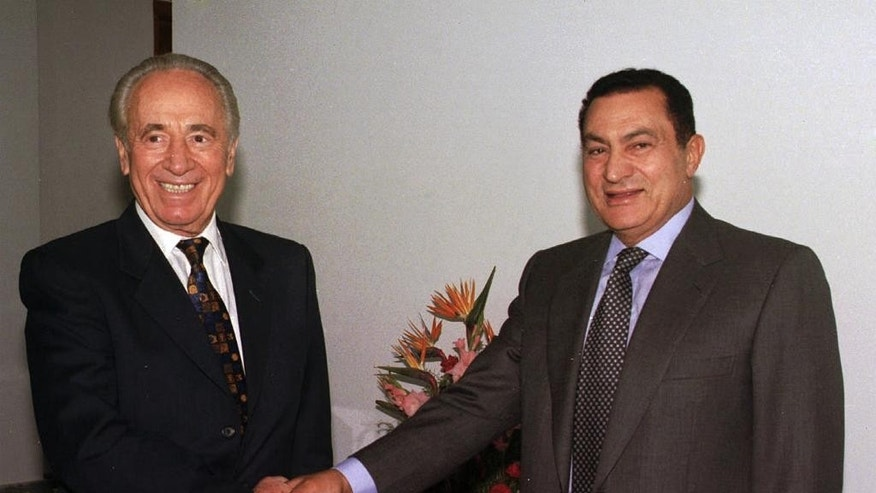 FILE - In this Oct. 1996 file photo, Egyptian President Hosni Mubarak, right, shakes hands with former Israeli Prime Minister Shimon Peres at the Sharm el Sheikh resort in the Sinai peninsula for talks on the Middle East peace process. Israel's Shimon Peres was widely admired around the world as a peacemaker and visionary but the view in the Arab world, which greeted his Sept. 28, 2016 death mostly with silence, was more complex: memories linger of another Peres  who waged war in Lebanon in 1996, organized Israel's secretive nuclear deterrent, and even supported the West Bank Jewish settler movement in the 1970s. (AP Photo/ Mohamed El-Dakhakhny, File)