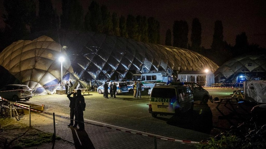 Police officers stand in front of an air-inflated structure which is a shelter for refugees in Berlin, Wednesday morning, Sept. 28, 2016. A 29-years-old man has been killed by police after a knife attack. (Gregor Fischer/dpa via AP)
