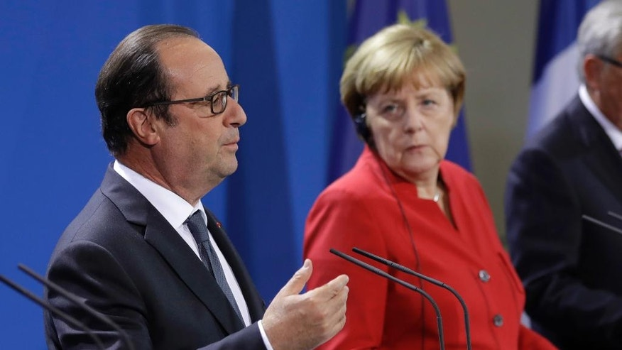 French President Francois Hollande speaks as German Chancellor Angela Merkel, right listens during press statements prior to a meeting of German Chancellor Angela Merkel, French President Francois Hollande and European Commission President Jean-Claude Juncker with representatives of the European Round Table of Industrialists in the chancellery in Berlin, Germany, Wednesday, Sept. 28, 2016. (AP Photo/Michael Sohn)
