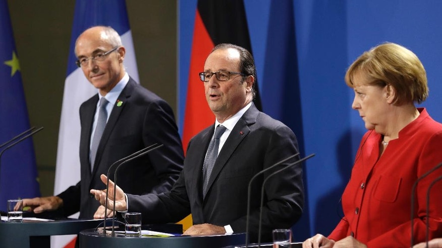 French President Francois Hollande is flanked by ERT Chairman Benoit Potier, left, and German Chancellor Angela Merkel during press statements prior to a meeting of German Chancellor Angela Merkel, French President Francois Hollande and European Commission President Jean-Claude Juncker with representatives of the European Round Table of Industrialists in the chancellery in Berlin, Germany, Wednesday, Sept. 28, 2016. (AP Photo/Michael Sohn)