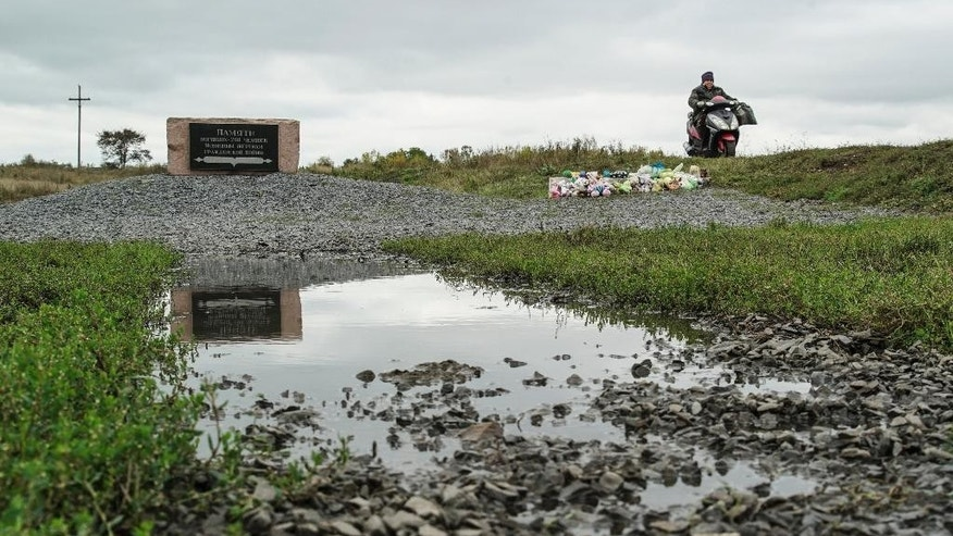 A woman rides her motorbike past the crash site of the Malaysia Airlines Flight 17, near the village of Hrabove, eastern Ukraine, Wednesday, Sept. 28, 2016. Dutch-led criminal investigators said Wednesday, they have solid evidence that a Malaysian jet was shot down by a Buk missile moved into eastern Ukraine from Russia. (AP Photo/Inna Varenytsia)