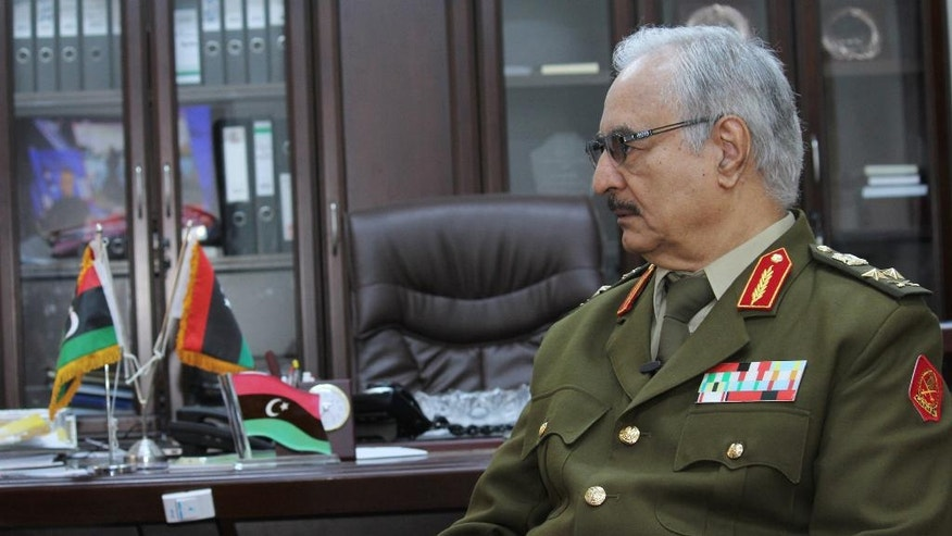 """FILE -- In this March 18, 2015 file photo, Gen. Khalifa Hifter speaks during an interview with The Associated Press in al-Marj, Libya. Hifter, a powerful Libyan general whose forces recently captured several key oil facilities has rejected a U.N.-brokered government and said the country would be better served by a leader with """"high-level military experience."""" In a series of written responses to questions from The Associated Press this week, Hifter said his army only recognizes the authority of the Libyan parliament based in the east, which has also rejected the U.N.-backed government in the capital, Tripoli. (AP Photo/Mohammed El-Sheikhy, File)"""