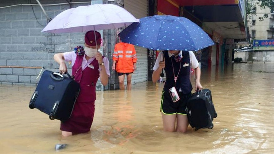 Train attendants carry their luggage as they walk through a flooded street in Fuzhou in southeastern China's Fujian Province Wednesday, Sept. 28, 2016. A massive typhoon made landfall in eastern China Wednesday, a day after carrying strong winds over Taiwan that felled trees and scattered debris, killing several people and injuring hundreds. (Chinatopix via AP)