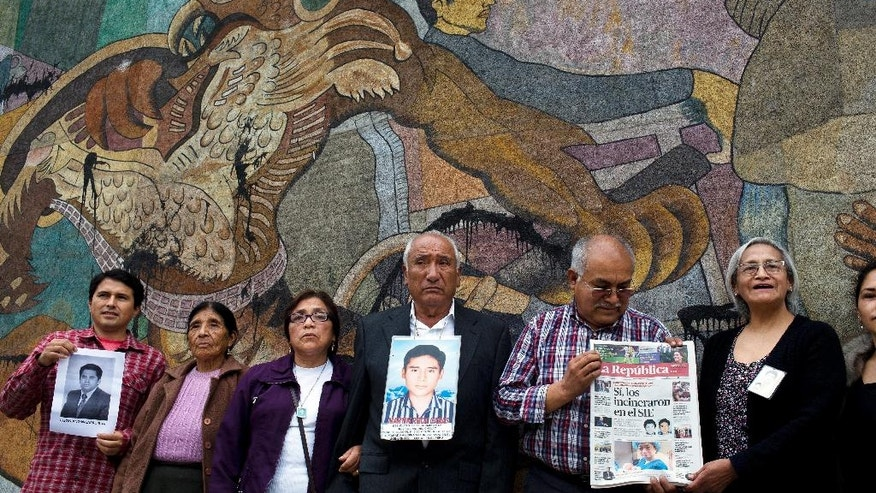 Relatives of two university students and a professor disappeared by security forces in 1993, pose for the picture after a press conference in Lima, Peru, Wednesday, Sept. 28, 2016. Former Peruvian spy chief Vladimir Montesinos has been sentenced to 22 years in prison for the forced disappearance of the three in 1993. (AP Photo/Rodrigo Abd)
